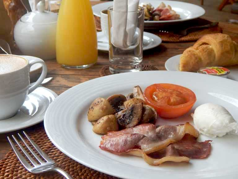 Breakfast plate with poached egg, bacon and mushrooms